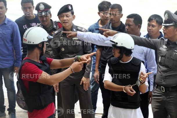 Two workers from Myanmar (wearing helmets and handcuffs), suspected of killing two British tourists on the island of Koh Tao last month, stand near Thai police officers during a re-enactment of the alleged crime, where the bodies of the tourists were found on Koh Tao island October 3, 2014. The two workers have admitted to killing David Miller and Hannah Witheridge, two British tourists, on the island in southern Thailand, police said on Friday, in a case that has threatened to further damage the Southeast Asian nation's already bruised tourism sector. The bodies of Miller, 24, and Witheridge, 23, were discovered on a beach on the island of Koh Tao, or Turtle Island, on Sept. 15 close to the hotel where they were staying.    REUTERS/Stringer (THAILAND - Tags: POLITICS CRIME LAW) THAILAND OUT. NO COMMERCIAL OR EDITORIAL SALES IN THAILAND